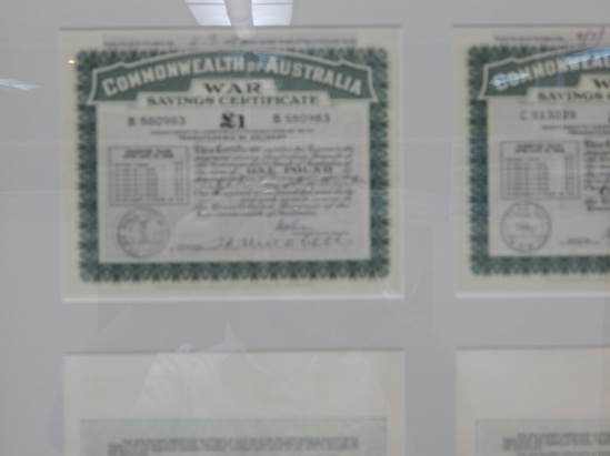 A copy of a War Savings Certificate that was issued in Peak Hill. There are two in the display and both were kindly donated to Parkes Shire Library by Joyce Stanford and Judy Barter. War Savings Certificates were a way for the Australian Government to raise much needed funds to support the war, and also for people unable to fight to contribute to the war effort. The best way to explain the concept of a war savings certificate to a younger audience is this - it's like a gift card but with compound interest. These War Savings Certificates were purchased in 1940 for 16 shillings (16s 0d) which is approximately $1.60 in today's currency. After seven years the certificate could be exchanged at the bank of issue for cash - these certificates are for one pound (£1) or approximately $2 today (source Reserve Bank of Australia Pre-decimal Inflation Calculator <a href=