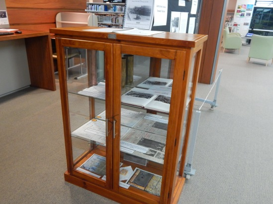 Display case containing items on loan courtesy of Parkes Historical Society. Inside are two artillery shells (one engraved in France during First World War), a copy of Ian Chambers' book Parkes: A Photographic History (belongs to Parkes Shire Library), newspaper clippings, War Service records and an Anzac biscuit and recipes.