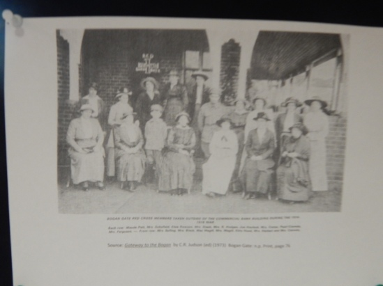 Photograph of Bogan Gate Red Cross members taken outside of the Commercial Bank Building during the 1914-1918 War Back row (left to right): Maude Pett, Mrs Schofield, Elsie Rowson, Mrs Stack, Mrs R Hodges, Joe Haylock, Mrs Coster, Pearl Coombs, Mrs Ferguson, ?. Front row: Mrs Solling, Mrs Black, Mac Magill, Mrs Magill, Kitty Hood, Mrs Herbert and Mrs Coombs. Photograph is from Gateway to the Bogan by C R Judson (Editor) and Parkes Shire Library has two copies - one of public catalogue for borrowing and another reference copy in the Family & Local History room.