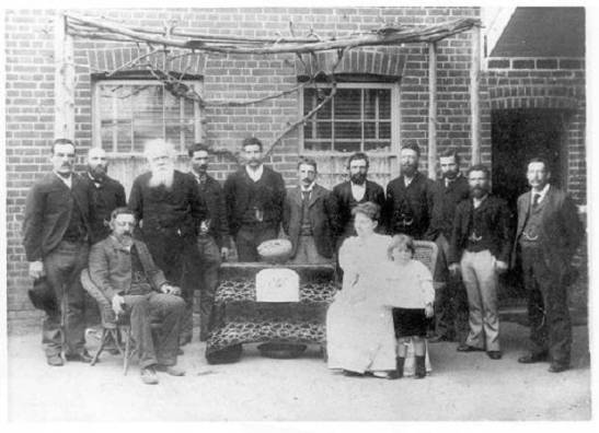 "Photograph of Henry Parkes on one of his many visits to the Shire that would one day bear his name. The sign in front of the gold (now faded) originally read 'New Bushman's Hill Tribute - Parkes. ""The Lady Parkes"" 1347 oz' In this photograph (standing, left to right) T Faull, J Mackay, Sir Henry Parkes, D Jones, H Ensor, Albert William Buzzacott (local manager of the Bank of Australasia), R Copp, M Fifield, J Warn, J Faull, HS Harwood, (sitting) R Wright (Mine Manager), Lady Eleanor Parkes and son Charles Henry. Source: Parkes: A Photographic History by Ian Chambers, 1988 Self-published: Parkes, NSW page 45"
