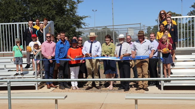 Two major infrastructure projects were showcased in Trundle - a new amenities complex at Trundle Showground; and completed upgrades to Berryman Oval. Present for the ribbon cutting was the Hon. Rick Colless, Parliamentary Secretary for Western NSW. Pictured in the photograph are (front row, left to right): Ben Howard (PSC), Peter Kelly (Trundle Progress Association), Cr Barbara Newton, Rick Colless MLC, Kate Hazelton (Nationals Candidate for Orange), Cr Ken Keith OAM, Andrew Rawsthorne (Trundle Progress Association), Gus White (Felton Industries - one of the suppliers, they did the grandstand seating). Other people in the background include Trundle Central School Students, Trundle Boomers Rugby League Football Club, Council's Presentation team, Trundle ABBA Festival. Photograph by Katrina Dwyer (Parkes Shire Council) taken on February 21, 2019.