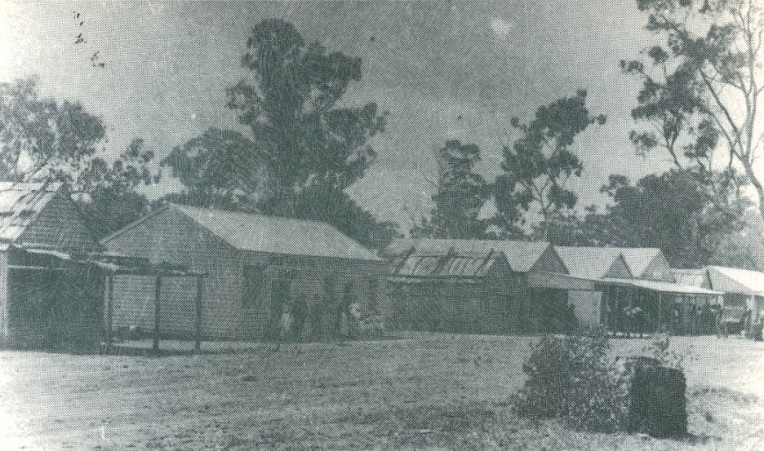 Reproduction of a photograph of the main street in Alectown in 1893. The view is looking north. This photograph is on the back cover of one of Len Unger's historical booklets. The buildings are (from left to right) Barnett's Butchery, McGee and Quinn's Bakery, Bark Shop, Foster's Original Store, Club House Hotel (with double gables), Bark Building used for school purposes in 1890, Miner's Exchange Hotel, Fletcher's Billiard Saloon. Source: Unger, L. A. (1983). Stories of Alectown: historical - humorous - tragic Parkes, N.S.W.: Parkes & District Historical Society