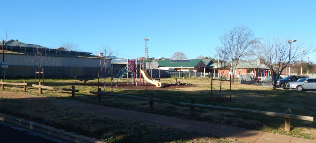 Photograph of AE Fox Park, with photographer on Armstrong Street. The playground equipment is a popular spot for young children and their parents, with Parkes Early Childhood Centre in the background. Photograph by Dan Fredericks (Parkes Shire Library) taken on July 21st, 2017