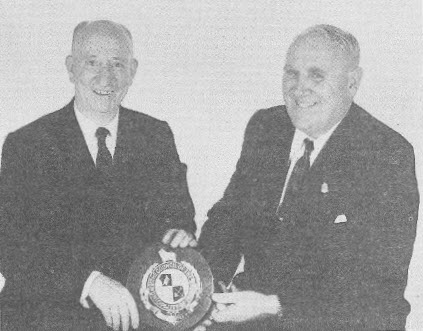 Alfred Fox (left) with Ald. A C Moon, MBE Mayor of Parkes holding the Commemorative Plaque presented to the Coventry City Council, England - the birthplace of Sir Henry Parkes. Source: Honour The Pioneers: 75th Anniversary of the Constitution of the Municipality of Parkes