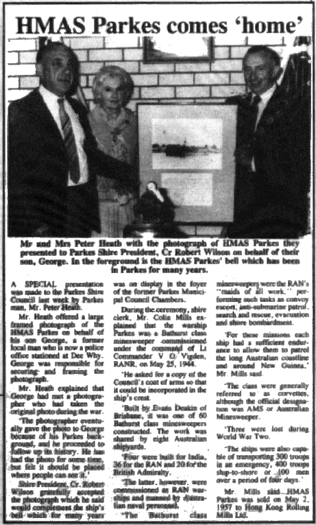 A framed photograph of HMAS Parkes is presented to Shire President Robert Wilson by Mr and Mrs Peter Heath. They are posing around the bell of HMAS Parkes, which today resides in Parkes Library. Source: Parkes Champion Post Monday, May 21, 1990 page 1