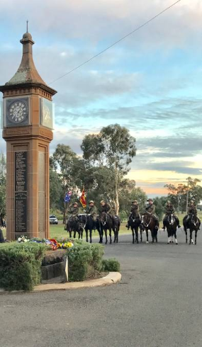 Photograph of ANZAC Day service at Bogan Gate in 2017. The Trundle Troop of the 6th Light Horse are in the background as dawn breaks. Source: Parkes Champion Post website