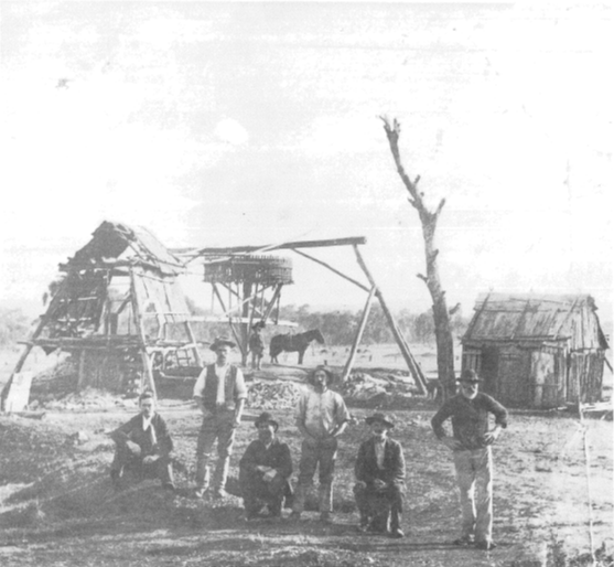 Ian Chambers noted that this photograph is of Dayspring Mine at Currajong (now called Parkes) in 1890. Owner Owen J Howard is sitting down at left with some of the miners (names unknown). This photograph shows in detail the above-ground methods employed in operating a substantial mine at that time, with good examples of the bush carpenter's trade. In the background the whim, or vertical capstan-like drum, is turned by the horse harnessed to the whim-pole. Wound around the drum is a cable which extends across to a pulley positioned above the mine and then down the shaft. By reversing the direction of the horses's circular path, the whim is thus used to raise or lower workmen, equipment and wash-dirt or ore. Photo by Harry McDade of Parkes. Source: Ian Chambers (1988) p.36